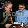 At left, MVB writer James Buchannan with 40 under 40 pick, Brad MacDougall of Andover, vice-president of<br /> government affairs for the Associated Industries of Massachusetts, look over the premier issue of MVB Business Magazine,<br /> at the MVB Business Magazine Release Party, Friday, at Glory Restaurant, Andover.<br /> 10-22-10,  Photo by Frank J. Leone, Jr.