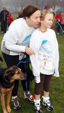 "Andover:  Jeanie Liddell and her daughter Sabria, 7, along with dog ""Ginger"", joined in the race, all are from  Andover,<br /> at the Feaster Five Road Race, Thanksgiving morning, Shawsheen Square in Andover.<br /> 11-26-09                         Photo by Frank J. Leone, Jr."