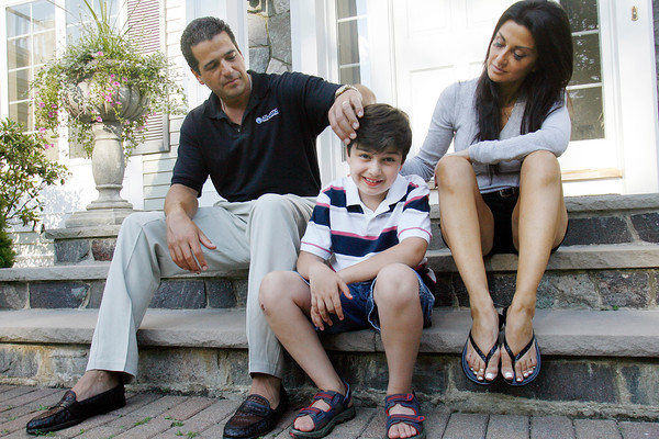 Andover:<br /> Charlie Alex, 8, sits with his parents Jim and Angela Alex Tuesday afternoon in front of their home in Andover. Charlie is autistic and will be present July 28th for the 3rd Annual Fore Melmark New England, a golfing fundraiser started by his parents for Melmark which is a school serving children with autism and other challenging behaviors. <br /> Photo by Roger Darrigrand/Eagle-Tribune Tuesday, July 15, 2008