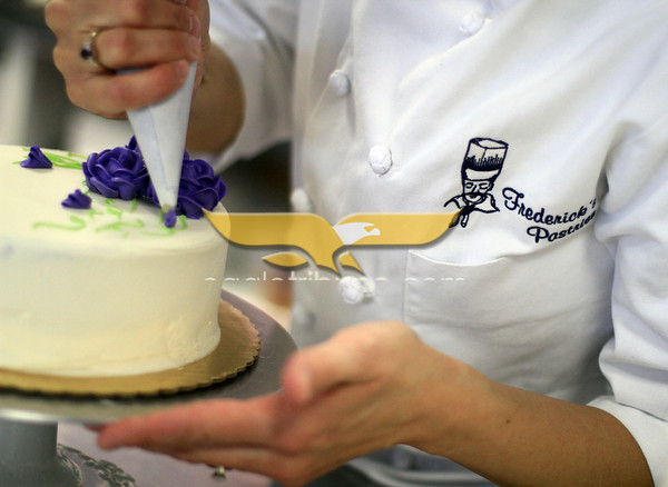 Susan Robert, owner of Frederick's Pastres in North Andover, ices a cake. Photo by Angie Beaulieu.