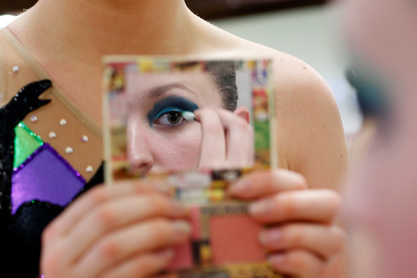 A teammate holds a mirror for Laura Schmidt has she puts on her eye shadow. <br /> Photo by Mary Schwalm.