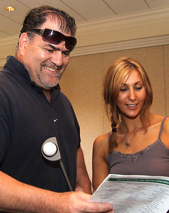 Stan Krol of Andover, event sponsor and Hillary Woodland of North Andover, look over the evening's program, at the Melmark of New England Golf Tourney, Monday, at Andover Country Club.