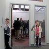 "MARY SCHWALM/Staff photo  Alex Feil, 8, left, and his sister Olivia, 6, greet visitors as they arrive at Theia Studios in North Andover for the opening of a show of Damian Strohmeyers work ""A Lifetime of Sports Photography""  3/15/15"