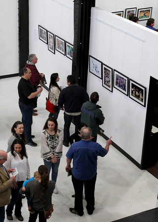 "MARY SCHWALM/Staff photo Members of the community look at a collection of photographs by professional sports photographer Damian Strohmeyer at the opening of his show ""A Lifetime of Sports Photography"" at the Theia Studios in North Andover.  3/15/15"