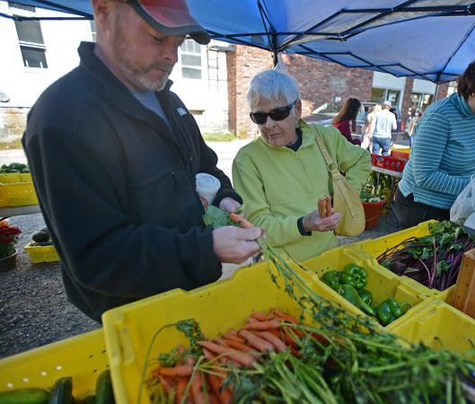RYAN HUTTON/ Staff photo<br /> Bob Hughes and his mother Peg shop for carrots from Boston Hill Farm  the Andover Farmer's Market.