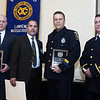 CARL RUSSO/Staff photo. STEPPING OUT: From left, Mass State Police Trooper, Kyle Flanagan, Exchange Club of Lawrence President, Francisco Santiago, North Andover police officer, Michael Gilligan and North Andover police Lt. Charles Gray. Trooper Flanagan and officer Gilligan were honored by the Exchange Club of Lawrence as Police Officers of the Year for jumping into the fast current of the Merrimack River to save a woman from drowning. This is the Exchange Club's 54th. annual Public Safety Award ceremony which is sponsored by Wheelabrator of North Andover. 1/21/2016.