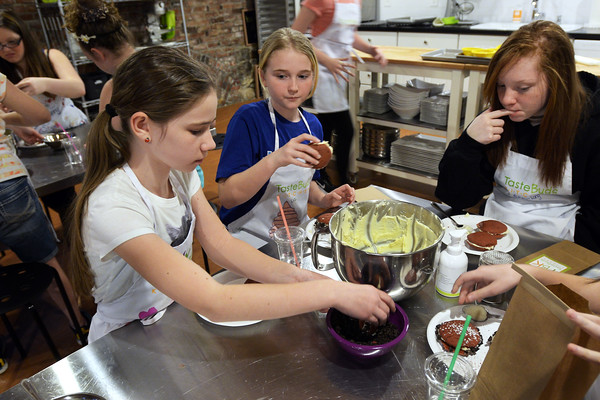 CARL RUSSO Staff photo. From left, Lily Seville and Liz Faulkner, both 11 and Autumn Long, 12 all of North Andover fill their red velvet whoopee pies with cream cheese frosting and dip them in the crushed Oreo cookies. The students are learning to bake at the Taste Buds Kitchen cooking school for kids in North Andover. 3/09/2016