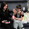 Hadley Goodman, 15, helps her brother Kane Goodman as he puts on his hockey gear.<br /> Photo by Paul Bilodeau