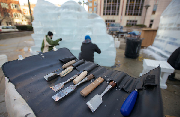 Carving tools sit on top of a block of ice as the crew from Brilliant Ice Sculpture work on the carvings outside the Prudential Center on Boylston Street. Chapelle uses chain saws, chisels, knives, drills and a variety of smaller, finer tools to make the ice come alive.<br /> Photo by Ryan Hutton.