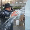 """Don Chapelle makes his own ice. A typical block of ice measures 40 by 20 by 10 inches and weighs about 300 pounds, he said. He uses a chainsaw on the ice sculpture """"Buffy"""" outside the Prudential Center on Boylston Street for the First Night celebration.<br /> Photo by Ryan Hutton."""