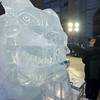 """Don Chapelle, owner of Brilliant Ice Sculpture, uses a chisel to craft the smile of """"Buffy"""", the seven-foot-tall bulldog he is carving outside the Prudential Center on Boylston Street. The piece includes a huge canine with a pink spiked collar and a dog house."""