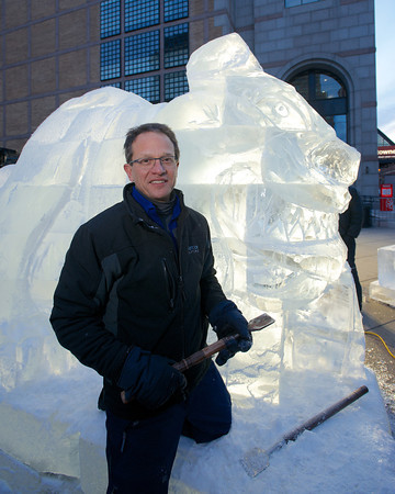 """Don Chapelle, owner of Brilliant Ice Sculpture, with """"Buffy"""", the seven-foot-tall bulldog he is carving outside the Prudential Center on Boylston Street. <br /> Photo by Ryan Hutton."""