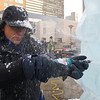 """Don Chapelle, owner of Brilliant Ice Sculpture, uses an electric chisel to carve out the teeth of """"Buffy"""", the seven-foot-tall bulldog he is carving outside the Prudential Center on Boylston Street in Boston.<br /> Photo by Ryan Hutton."""