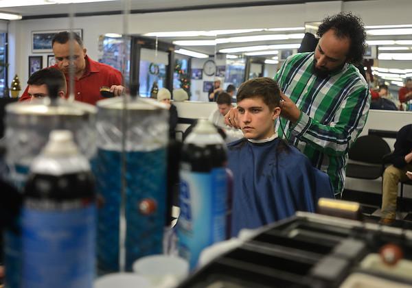 RYAN HUTTON/ Staff photo<br /> Barber David Perez cuts a customer's hair at the Andover Barber Shop.