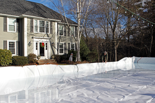 Rob Doherty pulls tight the plastic as he floods his backyard rink, in the front of his home, in North Andover. Doherty knows now not to lay his rink's 6-millimeter liner down until it's ready to be filled with water. Doing it beforehand can oftentimes result in sticks and stones ripping it or visiting deer tearing it to shreds, he says.<br /> MARY SCHWALM/Staff photo <br /> 12/29/14