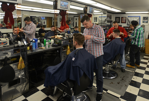 RYAN HUTTON/ Staff photo<br /> The crew of the Andover Barber Shop cut clients' hairs on a busy ay before Christmas.
