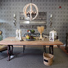"""AMY SWEENEY/Staff photo. The """"Industrial Look"""" such as the table made of rough boards and metal legs is popular now.  $1200<br /> Indoor/Outdoor sisal rug: $430<br /> Wooden Orb Chandelier: $475<br /> Paula Bakies, owner of Acorn Design Center in Andover.Sept. 25, 2015."""
