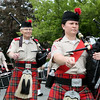 Amy McGlothin, front, marches with the Clan MacPherson pipes and drums march in the Andover Memorial Day parade.<br /> Photo by Amy Sweeney<br /> May 25, 2015