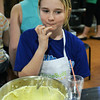 CARL RUSSO Staff photo. Liz Faulkner, 11 of North Andover savors the cream cheese frosting after a finger tip taste during baking class at the Taste Buds Kitchen cooking school for kids in North Andover. The frosting is for the red velvet whoopee pies the students were learning to make. 3/09/2016