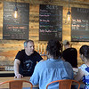 RYAN HUTTON/ Staff photo<br /> Oak & Iron Brewing owner Jim Cass speaks with customers behind the bar.