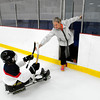 Tracy Goodman hands her son Kane Goodman a stick before a sled hockey workout.<br /> Photo by Paul Bilodeau