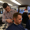RYAN HUTTON/ Staff photo<br /> Barber Roger Desharnais takes clippers to the back of customer Richard Maher's neck at the Andover Barber Shop.