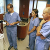 Angie Beaulieu photo. Mike, LaJuana and Fred Ravens look at a images on a device they frequently use with their dentistry practice.