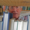 MARY SCHWALM/Staff photo Steven Schuyler looks through stacks of books at his book store in North Reading.  9/19/13