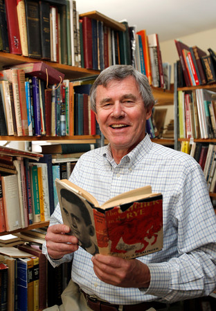 MARY SCHWALM/Staff photo Steven Schuyler smiles as he holds an original copy of Catcher and the Rye at his book store in North Reading.  9/19/13
