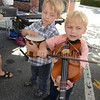 Jim Vaiknoras/staff photo. Twin brothers Mike and Evan Jenney, 5, try out the violin and bongos respectivaly. The intraments as well as others were  provided by the Creative Art Centerat  the Reading Fall Street Faire on Albiion Street.