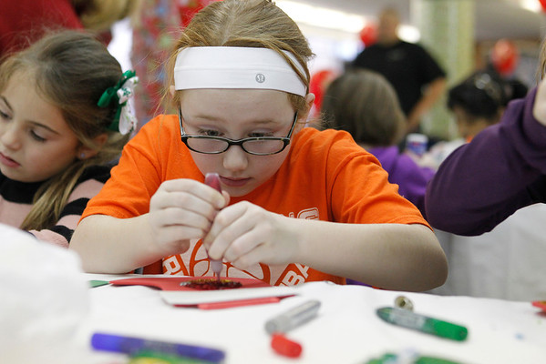MARY SCHWALM/Staff photo Michenzi McKenna, 9, of Reading, concentrates on her crafts at the Santa function at Austin Prep in Reading.  12/8/13