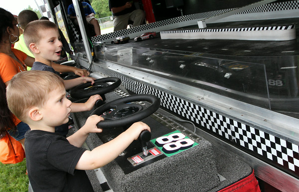 MARIA UMINSKI/READING MAGAZINE Brothers 5 year-old Miles and 2 year-old Christian Bhuta of Reading race cars around the track at Big Daddy's Racing tent during the Reading Friends and Family Day at Birch Meadow Park on June 14, 2014.