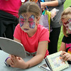 MARIA UMINSKI/READING MAGAZINE 6 year-old Caitlin DeRosa takes another look at her butterfly face paint as her 5 year-old sister Ashley DeRosa flips through a book of face paint creations during the Reading Friends and Family Day at Birch Meadow Park on June 14, 2014.