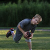 MIKE SPRINGER/Staff photo<br /> Eight-year-old Nik LaVerdiere of North Reading recovers his balance after catching a football thrown to him by his dad, Matt, during the weekly town barbeque and concert Wednesday, July 9 at Ipswich River Park in North Reading. The town holds the event every Wednesday evening for six weeks in the summer.