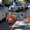 Lisa Mykyta of Reading crosses the finishline of the The Fall Street 5K one more time, this time with her two year-old Zorian Mykyta. Photo by Maria Uminski