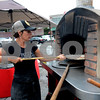 JIM VAIKNORAS/Staff photo Anna Peppe owner of Pizza Goddess in North Reading slides a pie into a portable brick oven at the Reading Fall Street Fair.