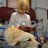 "RYAN HUTTON/ Staff photo<br /> Maeve Easler, 7, of North Reading, reads ""Clifford is a Star"" to Listening Lydia, a comfort dog brought to the Flint Memorial Library."