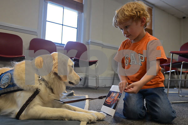 "RYAN HUTTON/ Staff photo<br /> Jack Healey, 4, of North Reading, shows the pictures in a book called ""Cool Cars"" to Listening Lydia, a comfort dog brought to the Flint Memorial Library."