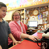 Corinne Fischer, Head of Children's Services at the Reading Public Library, helps six-year-old William Monteiro, of Reading, look for a book on Tuesday afternoon. DAVID LE/Staff Photo 1/28/14