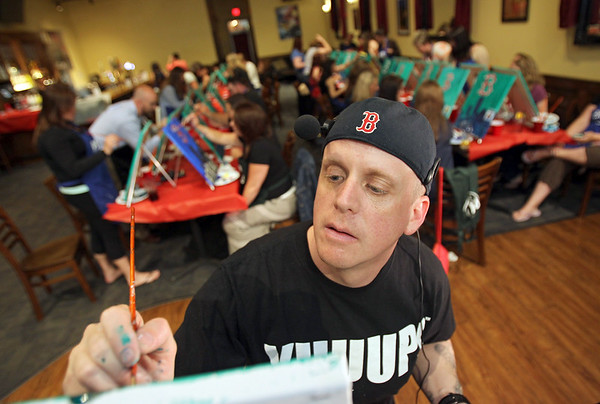 MARY SCHWALM/Staff photo Joe Cook, owner of Painting Under the Influence, works on his piece as he directs others during a painting lesson at The Great American Tavern in North Reading. 6/11/14
