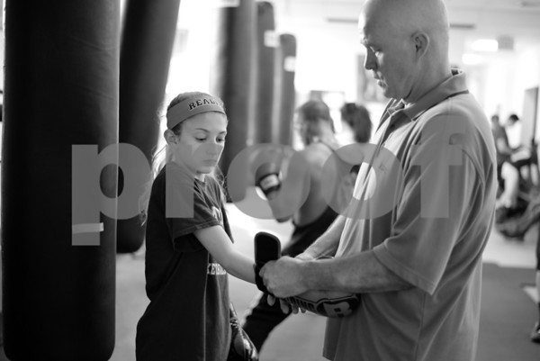 PAUL BILODEAU/Staff photo. Jim McNally helps Gianna Zagami, 12, with getting her gloves on at Jim McNally's Boxing in North Reading on Main Street.