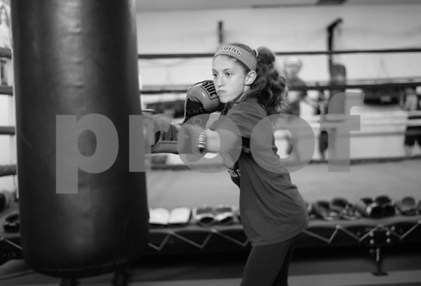 PAUL BILODEAU/Staff photo. Gianna Zagami, 12, works the heavy bag at Jim McNally's Boxing in North Reading on Main Street.