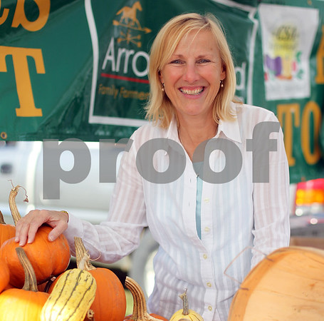 MARY SCHWALM/Staff photo  Claudia Brown poses for a photo with pumpkins at the North Reading Farmers Market at Ipswich River Park. 9/24/14