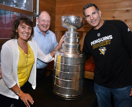 CARL RUSSO/Staff photo. READINGS MAGAZINE: Kathi and Pat Lee, owners of the Horseshoe Grille pose with the cup and Al Santilli of Reading, a pro-scout for the Pittsburg Penguins organization. The Stanley Cup, won by the Pittsburg Penguins in 2016 and 2017, was on display at the Horseshoe Grille in North Reading courtesy of Al Santilli of Reading, a pro-scout for the Pittsburg Penguins organization. 9/19/2017
