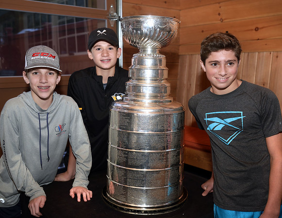 CARL RUSSO/Staff photo. READINGS MAGAZINE: From left, members of the Islanders Hockey Club of the Eastern Hockey Federation, Anthony Beaulieu, 13, of Lawrence, Luke Santilli, 12 of Reading and Brock James, 13 of Maine. The Stanley Cup, won by the Pittsburg Penguins in 2016 and 2017, was on display at the Horseshoe Grille in North Reading courtesy of Al Santilli of Reading, a pro-scout for the Pittsburg Penguins organization. 9/19/2017