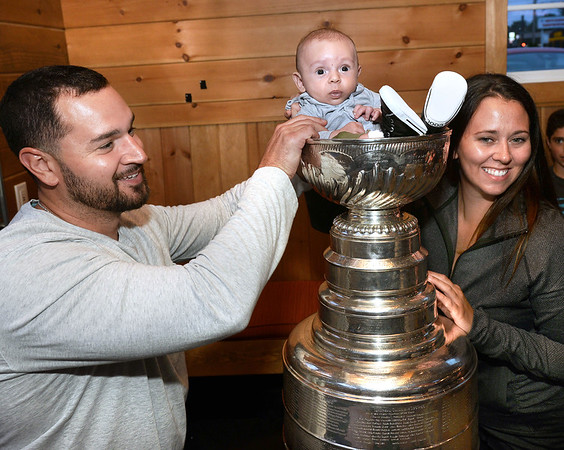 CARL RUSSO/Staff photo. READINGS MAGAZINE: Matt and Elizabeth Shea of Melrose place their two-months old son, Thomas inside the cup. The Stanley Cup, won by the Pittsburg Penguins in 2016 and 2017, was on display at the Horseshoe Grille in North Reading courtesy of Al Santilli of Reading, a pro-scout for the Pittsburg Penguins organization. 9/19/2017