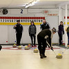 MARY SCHWALM/Staff photo Curlers sweep the path of the stone as teammates and their opponents look on during a curling match at the Nashua Country Club. 3/29/15