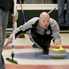 MARY SCHWALM/Staff photo Tim Muenier follows slides along the ice as he lines up the release of his stone during a curling match at the Nashua Country Club. 3/29/15