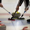 MARY SCHWALM/Staff photo Members of a team work together to sweep the path in front of the stone on its way to the house during their curling match at the Nashua Country Club. 3/29/15