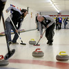 MARY SCHWALM/Staff photo Steve Welper, left, and Tim Muenier sweep the path in front of the stone on its way to the house during their curling match at the Nashua Country Club. 3/29/15